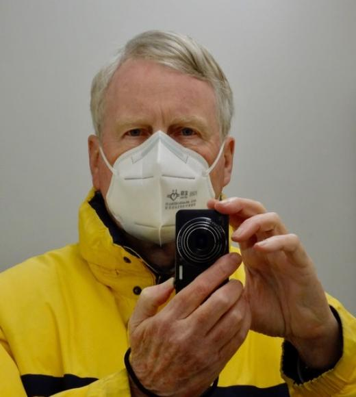 Eric Mann, wearing a mask, holding a camera
